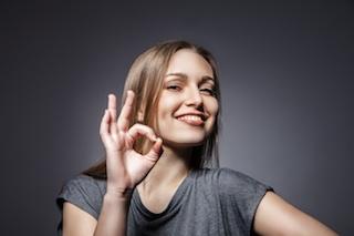 Smiling woman with okay gesture on dark grey